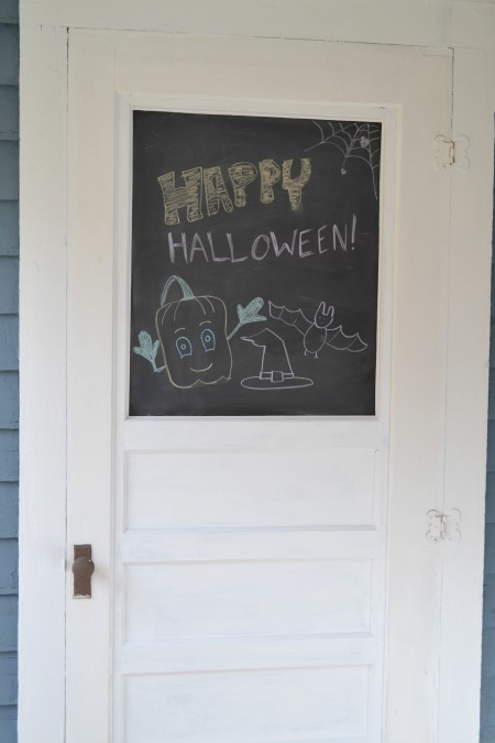 DIY outdoor chalkboard door with a happy halloween message including a pumpkin, witches hat, a bat, and a spider web